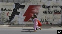 Bocah-bocah di jalanan Manama berlari membawa bendera Bahrain, Sabtu. Di belakang mereka, terlihat slogan-slogan anti-F1.