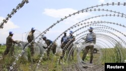 Le contingent sud-africain de soldats de la paix au Congo érige une barrière de fils barbelés autour de l'aéroport de Goma en RDC, le 26 novembre 2012.