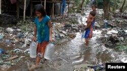 Trẻ em khiêng nước đi ngang qua đường phố lầy lội ở Batangas, phía nam thủ đô Philippines.