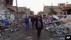 Penduduk setempat meneliti kerusakan rumah-rumah setelah serangan bom mobil di Kirkuk, Baghdad (17/12). (AP/Emad Matti)