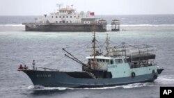 Sebuah kapal nelayan melintasi wilayah karang Meiji dekat propinsi Hainan di Laut China Selatan (Foto: dok). Vietnam menuduh China merusak sebuah kapal nelayan, setelah sebuah kapal China menabrak kapal tersebut saat melintasi perairan Vietnam 20 Mei yang lalu.