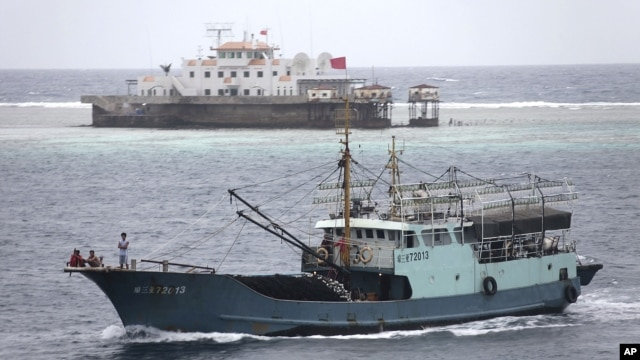 In this photo taken on July 20, 2012, a fishing boat sails past the Meiji reef off the island province of Hainan in the South China Sea. China's newest city, on a small, remote island in the South China Sea, is also claimed by Vietnam.