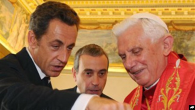French President Nicolas Sarkozy exchanges gifts with Pope Benedict XVI during a private audience at the Vatican, Friday, Oct. 8, 2010.