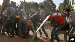 12月18日在开罗解放广场附近的埃及抗议者在与军队的冲突中躲藏在自造掩体的后面