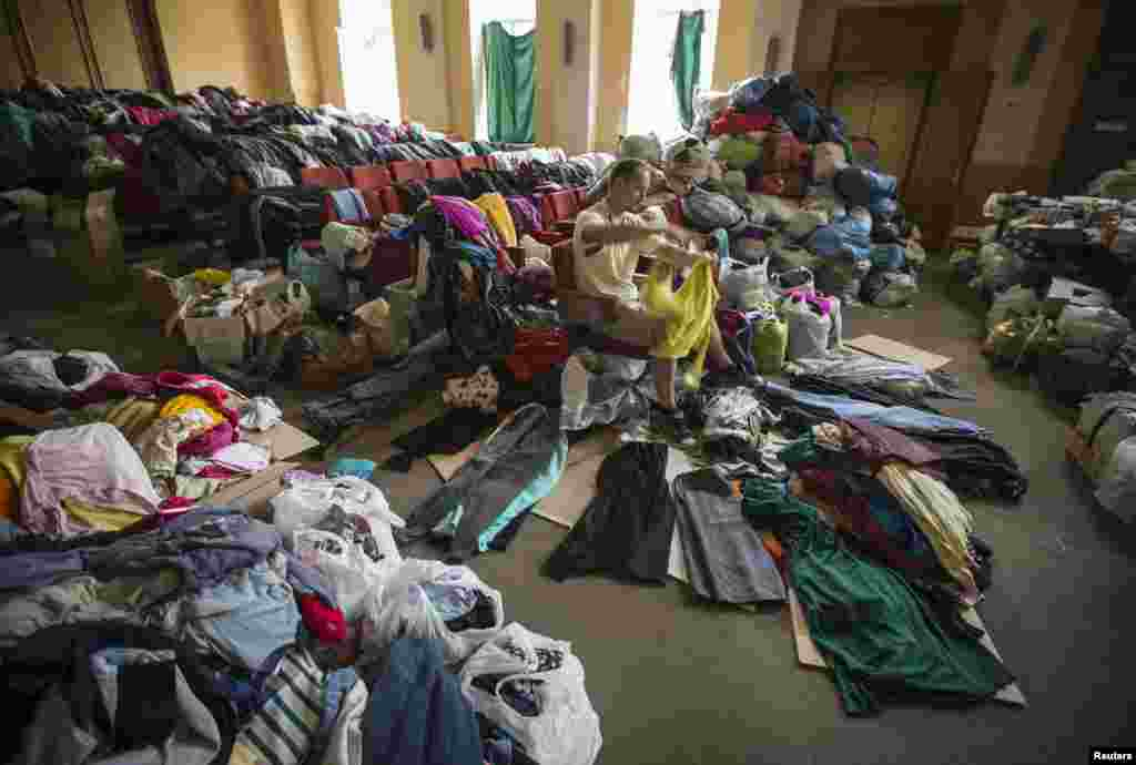 A man sorts donated clothes at a former concert hall converted into a center for collecting humanitarian aid for refugees in Donetsk, Ukraine, June 26, 2014.