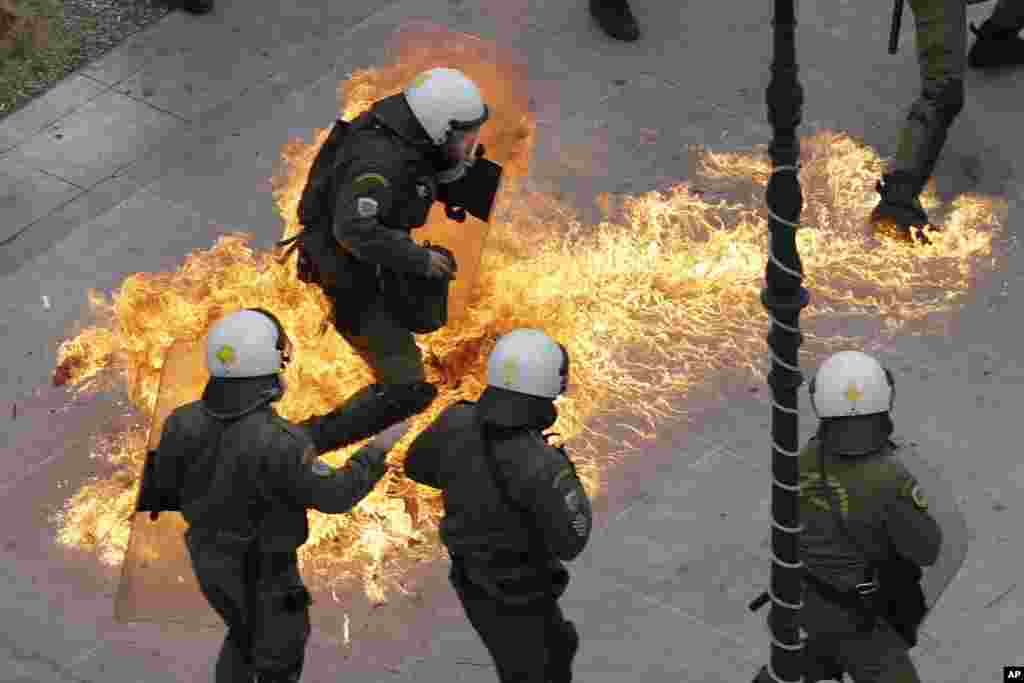Riot policemen try to avoid a petrol bomb thrown by protesters during a 24-hour nationwide general strike in Athens, Greece. Clashes broke out between police and youths throwing fire bombs and stones, as tens of thousands of people march through central Athens to protest planned pension reforms.