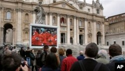 Para pengunjung menyaksikan penayangan misa di Gereja Basilica Santo Peter melalui layar monitor di Lapangan Vatikan. Misa ini diadakan sebelum para kardinal mengasingkan diri di dalam lapel Sistine dalam konklaf untuk memilih Paus baru, 12 Maret 2013. (AP Photo/Michael Sohn)