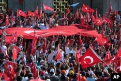 Turkish citizens wave their national flags as they protest against the military coup outside Turkey's parliament near the Turkish military headquarters in Ankara, Turkey, Saturday, July 16, 2016.