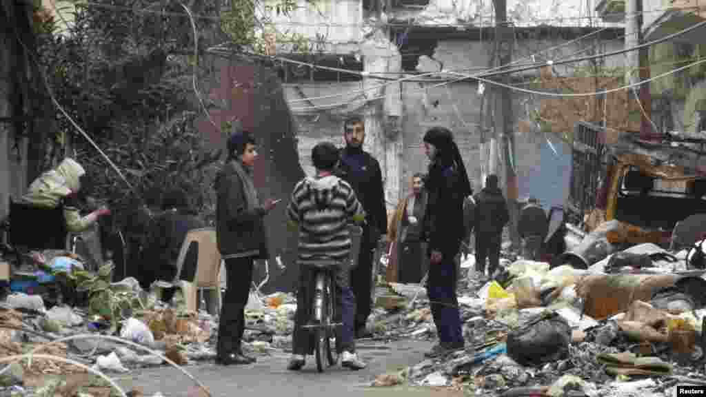 Civilians stand along a street amid garbage and rubble of damaged buildings in the besieged area of Homs, Jan. 27, 2014.