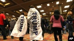FILE - Two teens wearing Donald Trump banners walk into the Reno Ballroom and Museum prior to Republican presidential candidate Donald Trump's rally, Jan. 10, 2016.