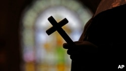 FILE - A silhouette of a crucifix is seen against the backdrop of a stained glass window inside a Catholic Church in New Orleans, Louisiana, Dec. 1, 2012.