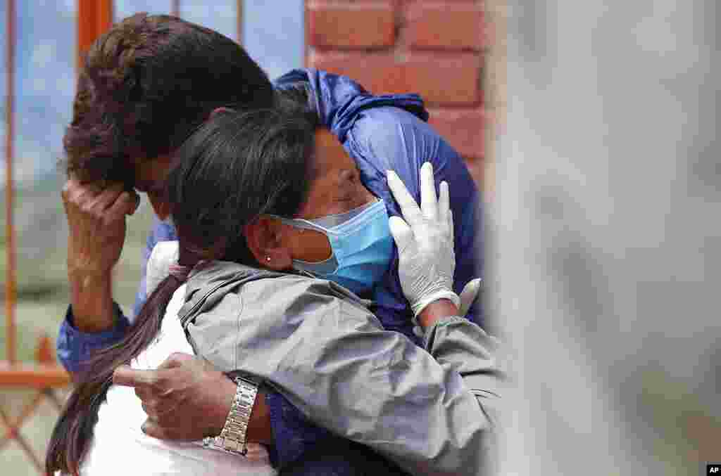 Relatives of a person who died of COVID-19 mourn at a crematorium in Kathmandu, Nepal, after an infection surge prompted the government to impose new lockdowns in major cities and towns.