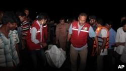 22일 방글라데시 다카 서부 지역에서 선박 사고가 발생한 가운데, 구조대가 선박 희생자들의 시신을 옮기고 있다.