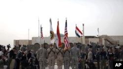 Tutar Amurka, da ta Iraqi da ta Rundunar Sojojojin Amurka a Iraqi a wurin bukin ayyana kawo karshen yakin Iraqi kafin a saukar da tutar Rundunar Sojojin Amurka a Iraqi, Alhamis 15 Disamba, 2011 a Bagadaza.