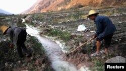 Para petani di distrik Dongchuan di Kunming, provinsi Yunan dekat aliran air sungai yang tercemar. (Foto: Dok)