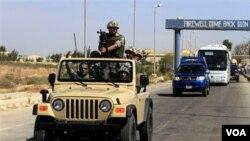 Tentara Mesir mengawal tahanan Palestina yang dibebaskan dari penjara dari penjara Israel ketika bis mereka melintas memasuki perbatasan Mesir (18/10).