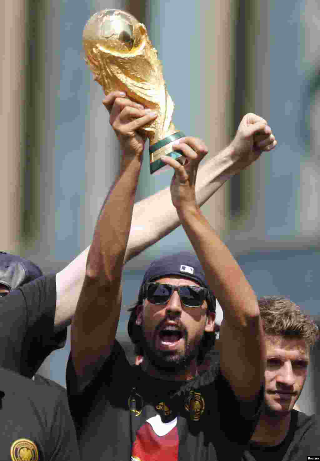 Germany's national soccer team player Sami Khedira lifts up the World Cup trophy on stage during celebrations to mark the team's 2014 Brazil World Cup victory, at the Fan Mile public viewing zone in Berlin, July 15, 2014.