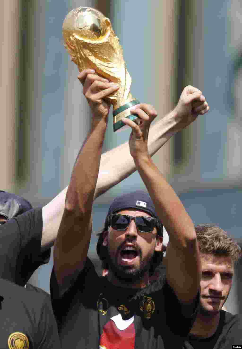 Pemain tim sepakbola nasional Jerman Sami Khedira mengangkat Piala Dunia di panggung dalam perayaan kemenangan mereka di Piala Dunia Brazil 2014, di tempat nobar Fan Mile di Berlin, 15 Juli 2014.
