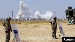 Turkish soldiers stand guard near the Mursitpinar border gate in Suruc in Sanliurfa province as smoke rises in the Syrian town of Kobani in the background, June 27, 2015.