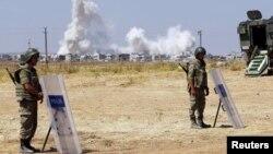 Binh sĩ Thổ Nhĩ Kỳ đứng gác gần cửa khẩu Mursitpinar ở Suruc, tỉnh Sanliurfa, trong khi khói bốc lên ở thị trấn Kobani, Syria, 27/6/2015.