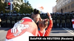 Belarus, Minsk, Opposition supporters with a historical white-red-white flag stay in front of law enforcement officers