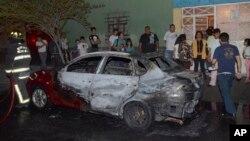 Warga setempat berkerumun di depan kendaraan yang sebagian terbakar setelah insiden penembakan di wilayah Tepito, Mexico City, Kamis 6 Juni 2013. (AP Photo). Tiga orang dilaporkan tewas dalam insiden tersebut.