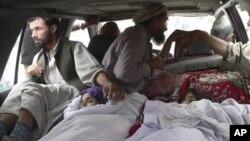 Warga di distrik Alingar, provinsi Laghman, Afghanistan membawa para perempuan korban serangan udara NATO ke rumah sakit setempat hari Minggu (16/9).