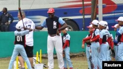 Tampa Bay Rays hitting coach Derek Shelton, left, and retired Cuban player Michel Ford (25) hold a baseball clinic for Cuban children the day before the Rays are to play an exhibition game against the Cuban National Team in Havana, Cuba, March 21, 2016.