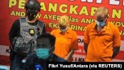 Buronan Interpol asal Rusia Andrei Kovalenka (kanan) berdiri di samping rekannya Ekaterina Trubkina, usai ditangkap, saat jumpa pers di kantor imigrasi Badung, Bali, 24 Februari 2021. (Foto: Fikri Yusuf/Antara via REUTERS)