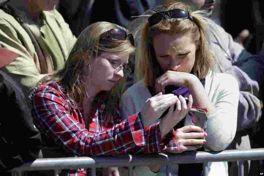 Nursing students Katie Robinson, left, and Megan Beach listen to a broadcast on their phones outside an interfaith service attended by President Barack Obama at the Cathedral of the Holy Cross, held in the wake of Boston Marathon explosions.