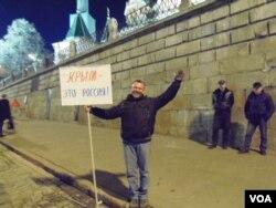 3月份在莫斯科红场举行了吞并克里米亚一周年的庆祝活动。一名参加者手举标语牌:克里米亚是俄罗斯的 (美国之音白桦)