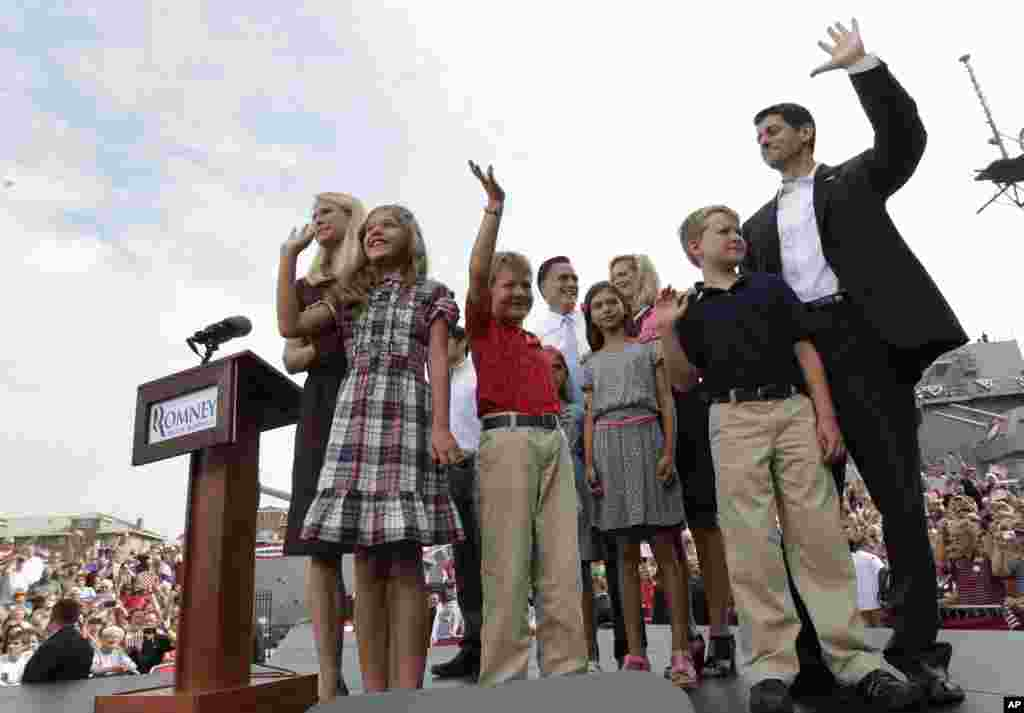 Paul Ryan, and his family, and Republican presidential candidate, former Massachusetts Gov. Mitt Romney and his family, partially visible at center back, wave to the crowd, Aug. 11, 2012, in Norfolk, Va.