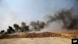 摩苏尔周围村庄在联军空袭后冒出的浓烟(2016年10月7日)