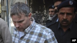 A U.S. consulate employee is escorted by police and officials out of court after facing a judge in Lahore, January 28, 2011