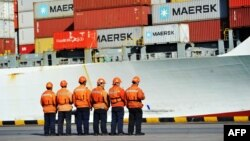 FILE - Workers stand in line next to a container ship at a port in Qingdao in China's eastern Shandong province, April 8, 2018.