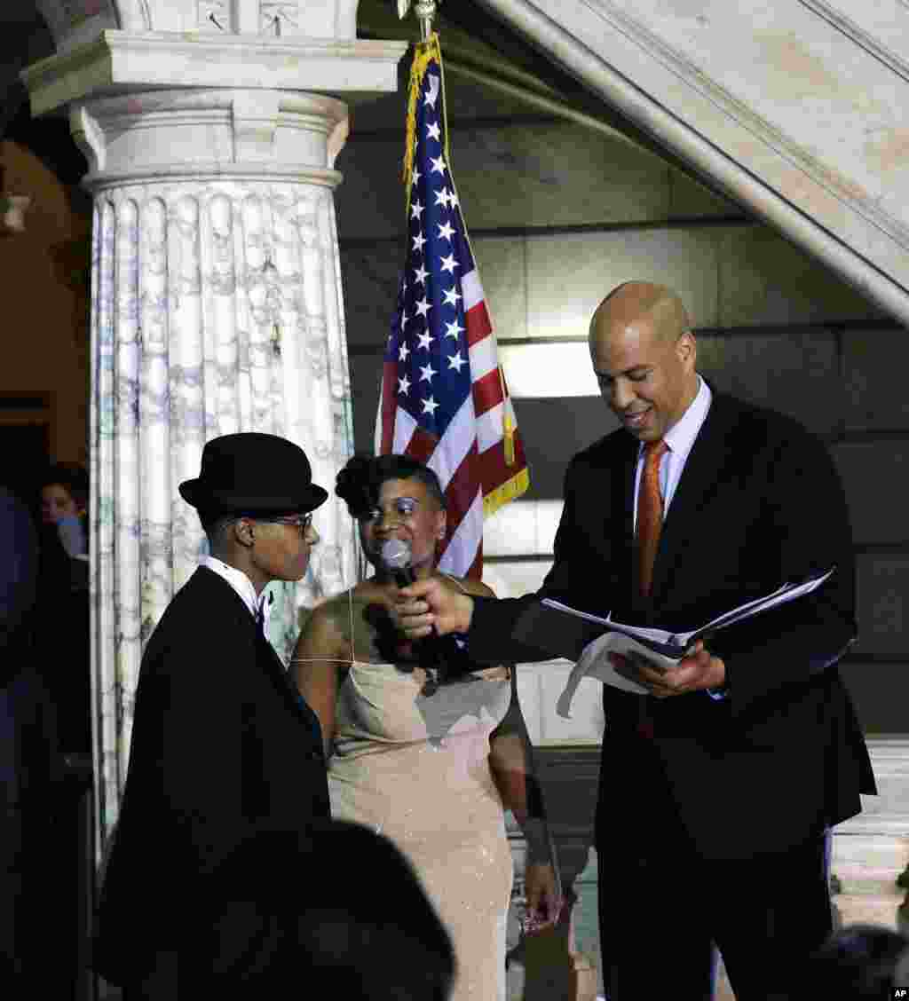 Newark Mayor and Senator-elect Cory Booker, right, officiates the ceremony for the same-sex marriage of Lydia Torres, left, 44, and Jenelle Torres, 42, center, at Newark City hall just after midnight.