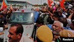 Narendra Modi, kandidat Perdana Menteri India dari partai Bharatiya Janata (BJP), memberikan 'salam damai' kepada para pendukungnya dari dalam mobil yang membawanya dari bandara New Delhi menyusuri pusat kota (17/5).