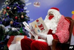 """A postal worker dressed as Santa, reads letters to addressed to """"Pere Noel"""" - Father Christmas in French - decorated with love hearts, stickers and glitter, in Libourne, southwest France, Monday, Nov. 23, 2020. (AP Photo/Francois Mori)"""