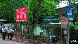缅甸街头各政党的竞选海报,左侧红色的为该地区民盟候选人,右侧绿色的是该地区巩发党候选人。(图片摄影:朱诺)