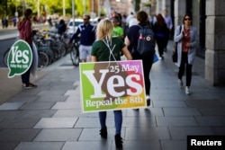 A woman carries a placard as Ireland holds a referendum on liberalizing abortion laws, in Dublin, May 25, 2018.