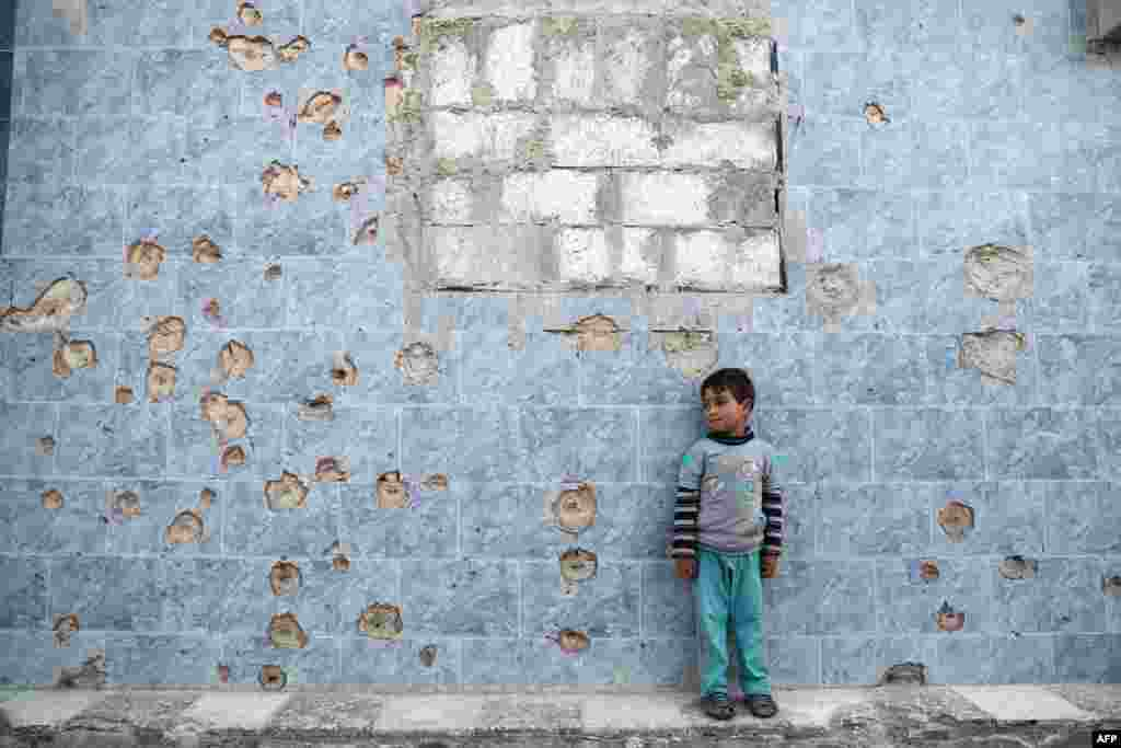 A Syrian boy stands against a wall covered in bullet holes, in the rebel-held town of Douma, on the eastern outskirts of the Syrian capital Damascus.