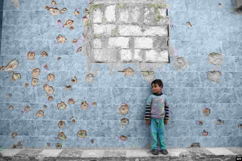 ក្មេងប្រុសស៊ីរីម្នាក់ឈរនៅក្បែរជញ្ជាំងដែលមានសុទ្ធតែស្នាមគ្រាប់កាំភ្លើង នៅក្នុងក្រុង Douma ដែលកាន់កាប់ដោយក្រុមឧទ្ទាម ប្រទេសស៊ីរី។