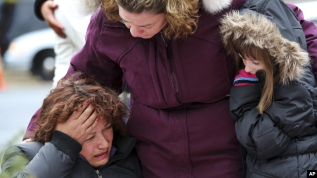 Mourners grieve at one of the makeshift memorials for victims of the Sandy Hook Elementary School shooting, Dec. 16, 2012, in Newtown, Conn.