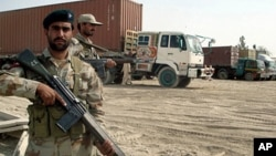 Pakistani paramilitary soldiers stand alongside trucks carrying NATO supplies at the border town of Chamam, Pakistan, September 30, 2010.