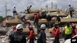 Para petugas penyelamat berusaha mencari korban di antara reruntuhan bangunan di Pedernales, Ekuador (19/4).