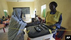 An elderly Southern Sudanese woman casts her vote Monday in a ballot box at a polling center in the city of Um Durman, Sudan, Jan. 10, 2011