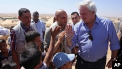 U.N. Under-Secretary-General for Humanitarian Affairs, Stephen O'Brien, greets Syrian refugees who fled civil war in their country, in the Zaatari Refugee Camp, near Mafraq, Jordan.