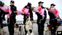 FILE - Chinese policewomen with sniffer dogs pose with flowers received on International Women's day during the second plenary session of the National People's Congress held in Beijing, March 8, 2012.