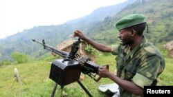 A M23 rebel fighter prepares his machine gun at their defense position in Karambi, eastern Democratic Republic of Congo (DRC) in north Kivu province, near the border with Uganda, July 12, 2012.