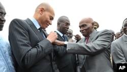 Abdoulaye Wade (à dr.) et son fils Karim (au c.) durant une cérémonie à Dakar, le 19 janvier 2011